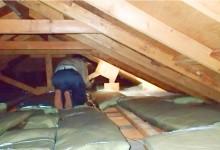 屋根裏の雨漏りを点検する作業員